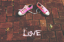 pink converse on bricks and word love in chalk