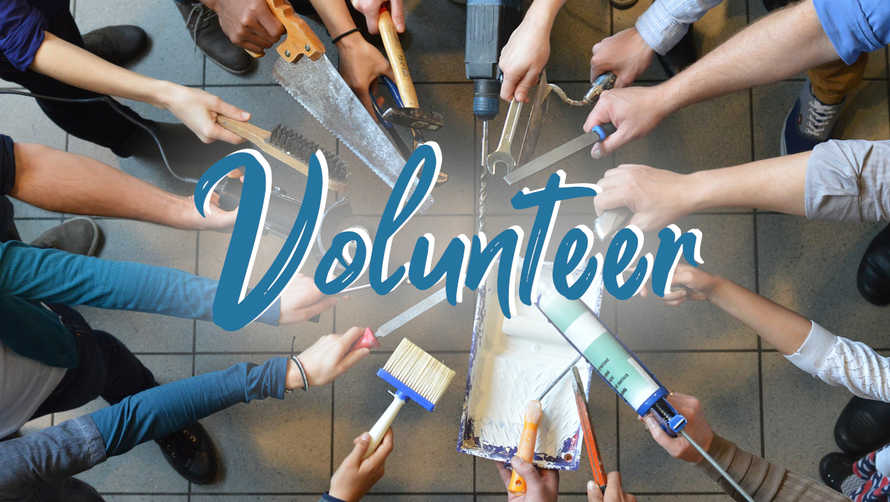 Volunteer Day – many people in a circle holding a lot of different work tools