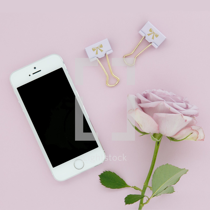 A cellphone, gold clips and a pink rose on a pink background.