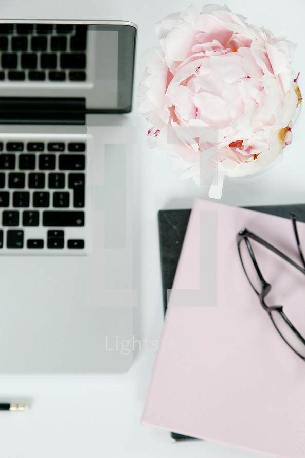stack of journals, laptop, pencil, and vase of flowers on a desk