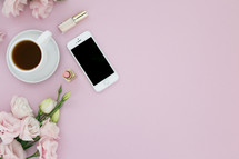 Cup of coffee, lipstick, cellphone and pink flowers on a pink background.