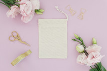 A linen pouch on a pink background surrounded by pink flowers.