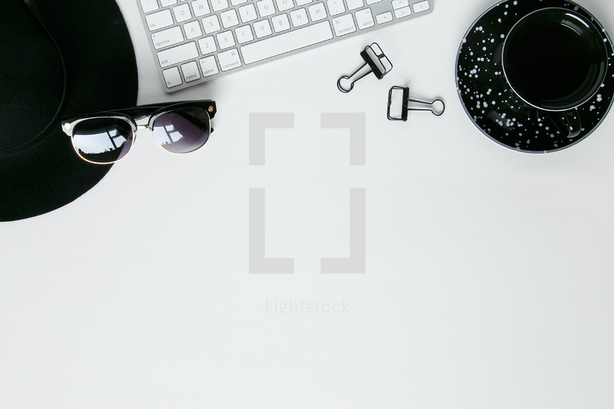 hat, sunglasses, clips, computer keyboard, and coffee border on a desk