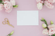 A blank white card on a pink background surrounded  by flowers and scissors.