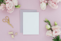 Blank notecards on a pink background surrounded by pink flowers.
