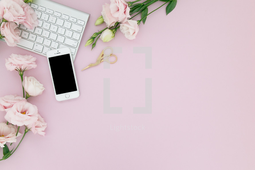 A computer keyboard, cell phone and flowers on a pink background.