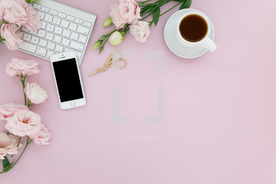 A computer keyboard, cell phone, cup of coffee and pink flowers on a pink background.