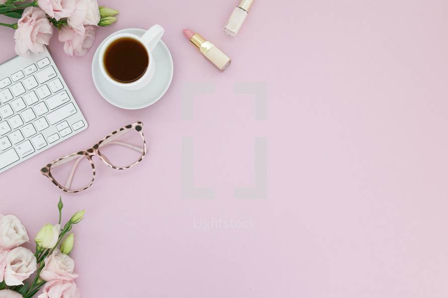 Computer keyboard, cup of coffee, eyeglasses, lipstick and pink flowers on a pink background.