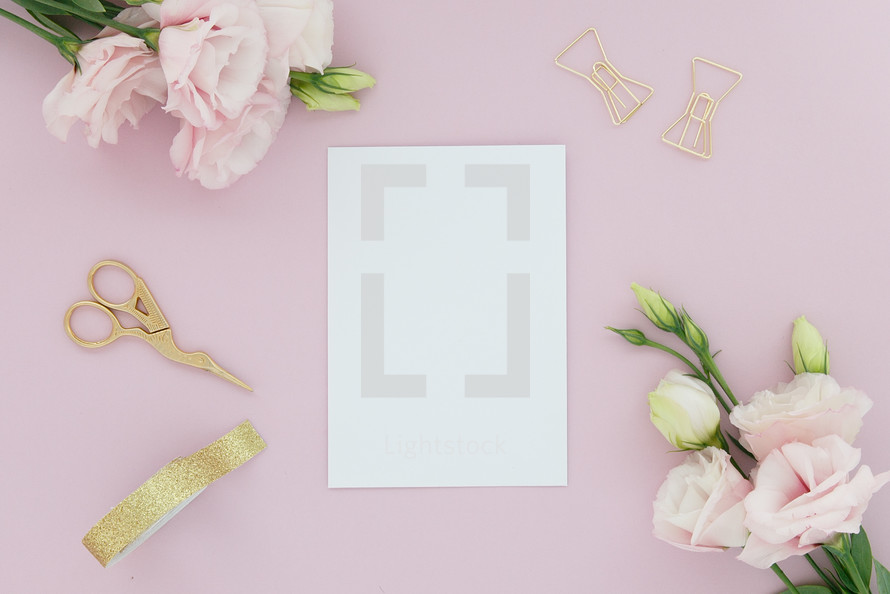 A blank white note card on a pink background surrounded by pink flowers.