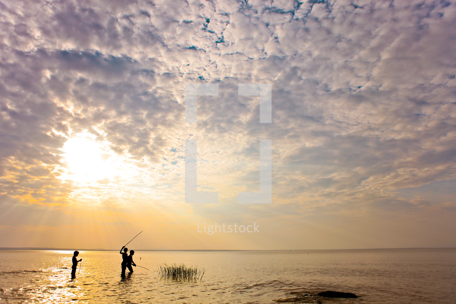 Children wading and fishing during a sunrise