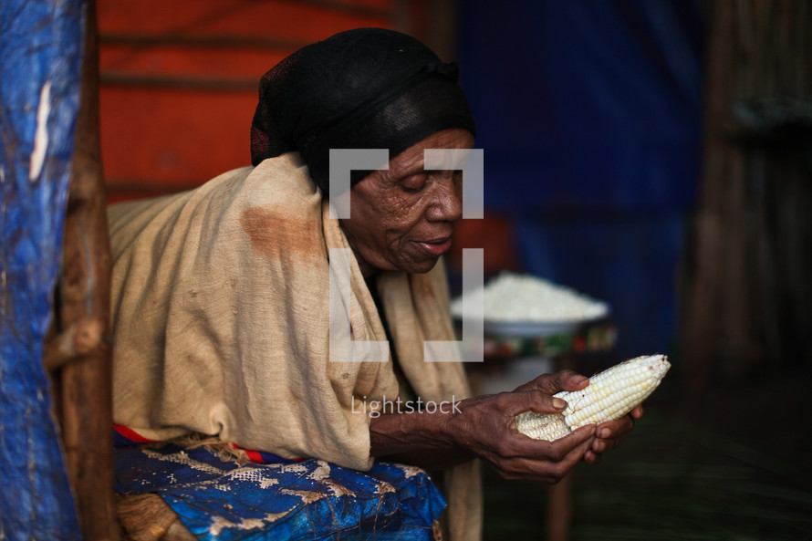 Elderly woman peeling corn