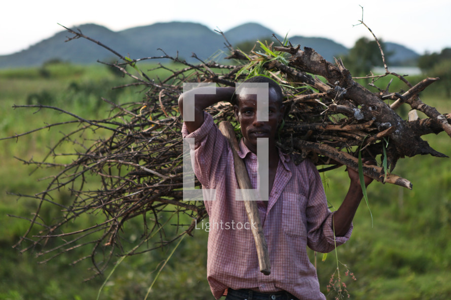 Man carrying branches over his shoulder