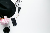 border of a hat, sunglasses, mug, flowers, and cellphone on a white background