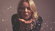 a woman blowing glitter in slow motion