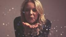 a woman blowing glitter in slow motion