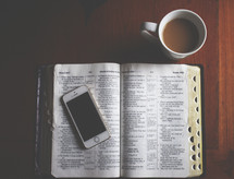 coffe mug and a cellphone on the pages of a Bible